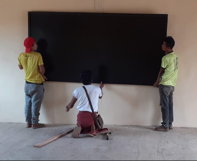 Putting up one of five blackboards in a classroom