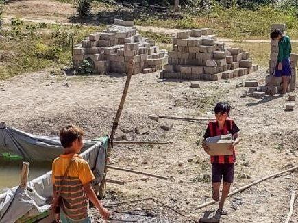 Young volunteers help carry bricks